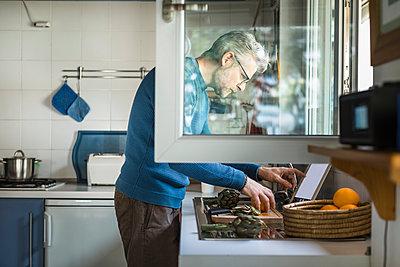 Mature man preparing artichoke in his kitchen using digital tablet - p300m2180436 by 27exp