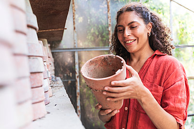 Smiling woman holding pot while standing in garden shed - p300m2220881 by Francesco Morandini