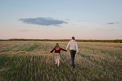 Father and daughter walking in field - p300m2281791 by Ekaterina Yakunina