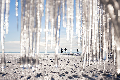 Silhouettes of people on beach. icicles on foreground - p312m1113972f by Henrik Trygg