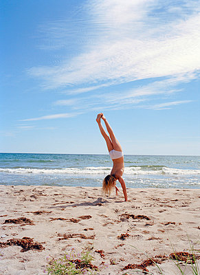 Girl doing handstand on beach, Gotland, Sweden - p312m872451 by Pia Ulin