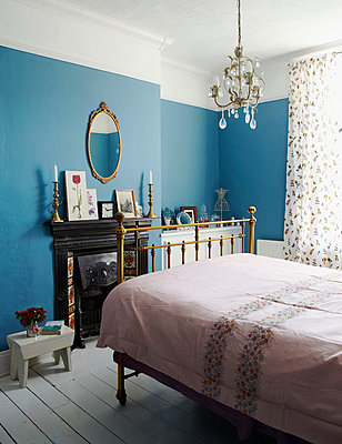 Brass bed with chandelier in turquoise bedroom of Edwardian terraced house - p349m789893 by Brent Darby