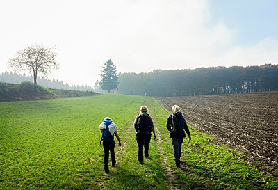 Rear view of mother and two children hiking along field path, Beaufort, Echternach, Luxembourg - p429m1103224 by Mischa Keijser