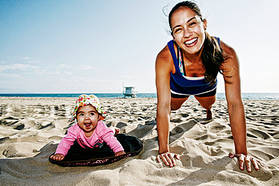 Mother and daughter doing push-ups at beach - p555m1305534 by Peathegee Inc