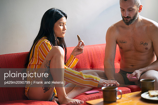 Hipster couple playing cards and having breakfast on sofa - p429m2090799 by Frank and Helena