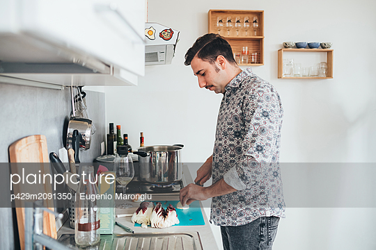 Man preparing food in kitchen - p429m2091350 by Eugenio Marongiu