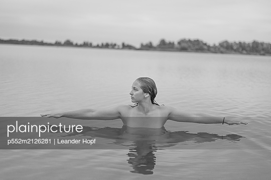 Young woman bathing in lake - p552m2126281 by Leander Hopf