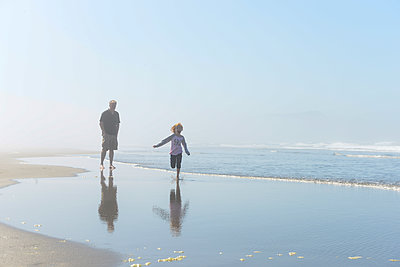Happy little redhead girl running along the ocean shore with Grandpa. - p1166m2279584 by Cavan Images