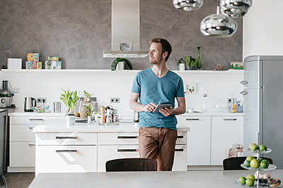 Man with tablet standing in the kitchen looking at distance - p300m1549596 by Kniel Synnatzschke