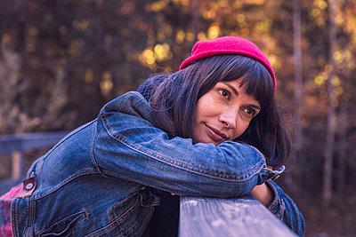 Woman wearing red woolly hat and denim jacket looking sideways - p300m2160397 von Studio 27