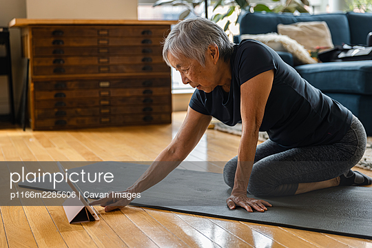 Senior woman using digital tablet while sitting on exercise mat in living room - p1166m2285606 by Cavan Images