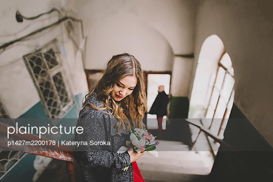 Bride standing on stairs while groom is waiting at entrance - p1427m2200178 by Kateryna Soroka