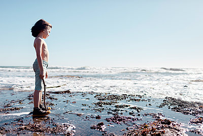 Side view of shirtless boy holding stick standing at beach against clear sky during sunny day - p1166m1416302 by Cavan Images