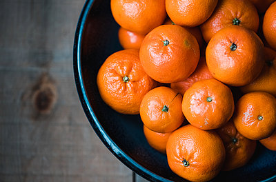 Close up of bowl of mandarin oranges on wooden table shot from above. - p1166m2094802 by Cavan Images