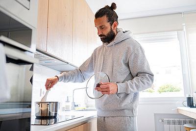 Handsome man preparing food in kitchen at home - p300m2281948 by Jose Carlos Ichiro