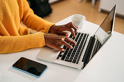Young woman typing while using laptop at home - p300m2282658 by Manu Padilla Photo