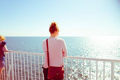 Junge Frau schaut nachdenklich aufs Meer - p432m2015694 von mia takahara