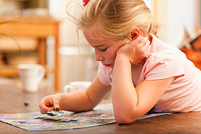Caucasian girl putting puzzle together - p555m1478219 by John Lund/Marc Romanelli