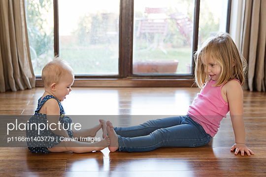 Sisters playing with sitting on floor by window at home - p1166m1403779 by Cavan Images