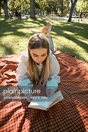 Teenage girl reading a book in the park - p1640m2258496 by Holly & John