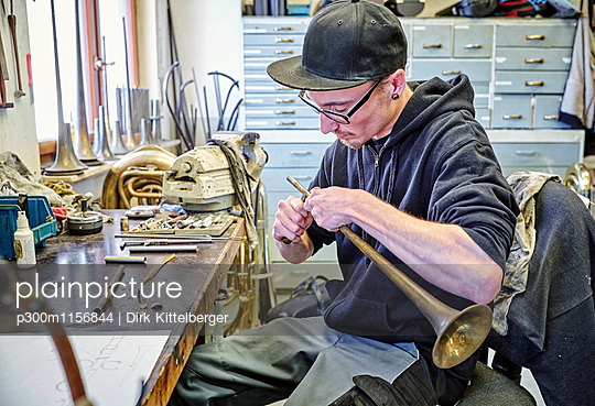 Instrument maker making trumpet in workshop - p300m1156844 by Dirk Kittelberger
