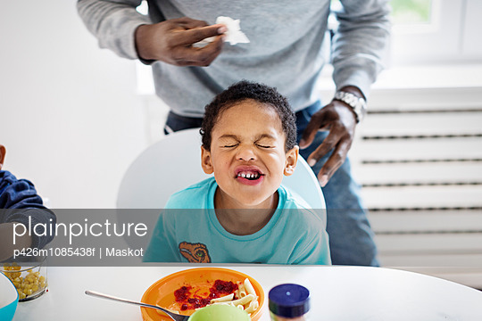 Boy making face while having food at table with father standing in background - p426m1085438f by Maskot