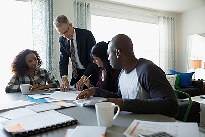 Financial advisor with paperwork meeting with family at dining room table - p1192m1201895 by Hero Images