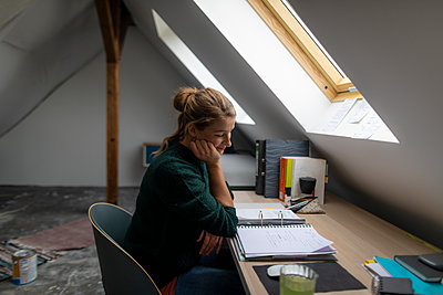 Young woman sitting at desk in attic studying folder - p300m2103189 by Gustafsson