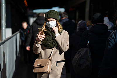 Woman with face mask standing at bus stop, using smartphone - p300m2170836 by Vasily Pindyurin