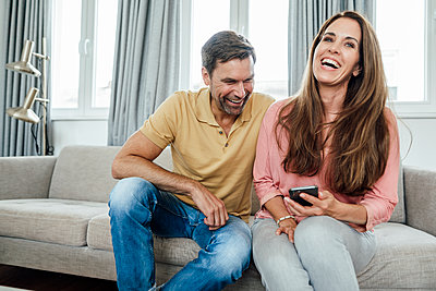 Mature man and woman laughing while sitting on sofa at home - p300m2243720 by Joseffson