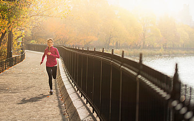 Asian woman running on waterfront path - p555m1414390 by JGI/Tom Grill