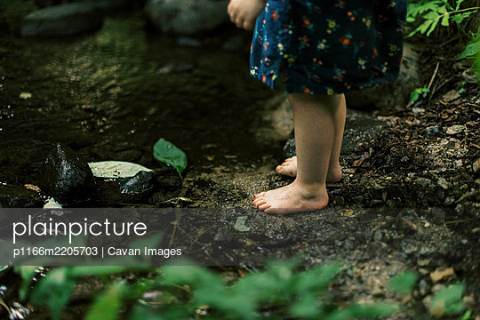 Two year old toddler girl standing at the shore of a woodsy river - p1166m2205703 by Cavan Images