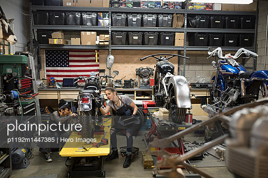 Female motorcycle mechanics fixing motorcycle in auto repair shop