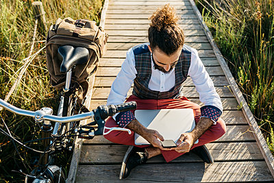 Well dressed man sitting on a wooden walkway in the countryside next to a bike with cell phone and laptop - p300m2131949 by Josep Rovirosa