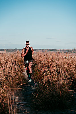 Sportsman running amidst dried plants against sky during sunset - p300m2250912 by Eva Blanco