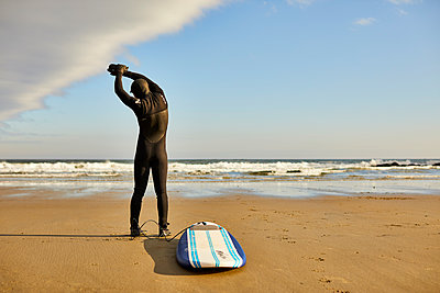 A Male Surfer Stretching And Warming Up Before Surfing At Beach - p343m1443991 by Josh Campbell