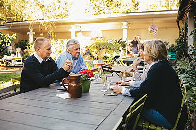Happy senior couples discussing at outdoor restaurant - p426m1143269 by Maskot