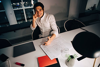 High angle portrait of smiling businessman sitting with blueprint at desk while working late in office - p426m2194752 by Maskot
