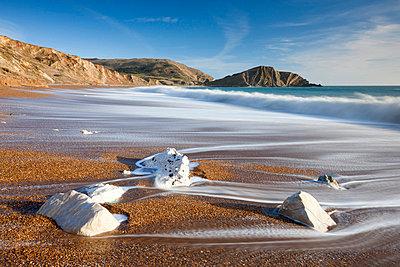 Waves wash clean the beautiful beach at Worbarrow Bay on the Jurassic Coast, UNESCO World Heritage Site, Dorset, England, United Kingdom, Europe - p871m711400 by Adam Burton