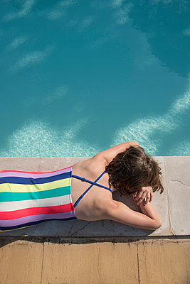 Girl sunbathing at the poolside - p954m1585911 by Heidi Mayer