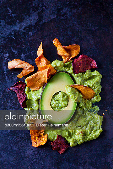 Guacamole, slice of avocado and vegetable chips on dark ground - p300m1581309 von Dieter Heinemann