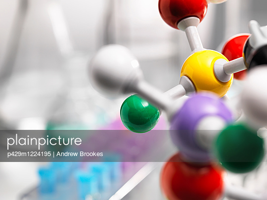 A molecular model of a chemical formula with laboratory equipment in the background - p429m1224195 by Andrew Brookes