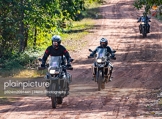 Male friends riding ADV motorcycles on dirt road in Cambodia - p924m2091441 by Henn Photography