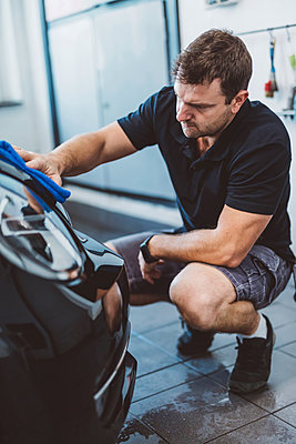 Male worker cleaning car with towel while crouching in workshop - p1166m2060379 by Cavan Images