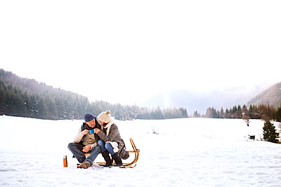 Senior couple sitting side by side on sledge in snow-covered landscape - p300m1505829 by HalfPoint