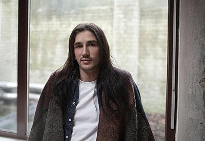 Mann mit langen Haaren steht am Fenster - p341m1218765 von Mikesch