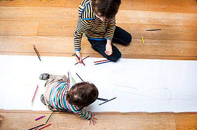 Overhead view of male toddler and big brother sitting on floor drawing on long paper - p429m1418482 by Bonfanti Diego