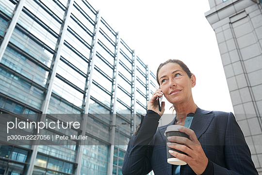 Smiling businesswoman drinking coffee while talking on mobile phone in city - p300m2227056 by Pete Muller