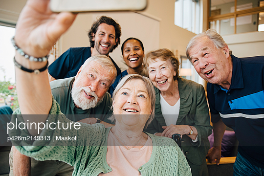 Senior woman taking selfie with friends and healthcare workers at retirement home - p426m2149313 by Maskot