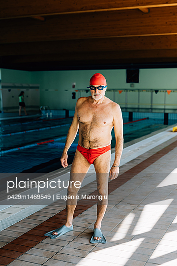 Senior man standing by swimming pool